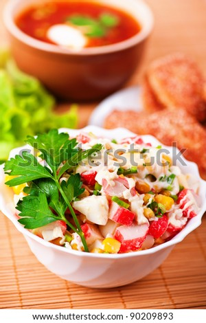close-up cooked dinner (salad of crab sticks, corn, eggs, mayonnaise, decorated with sprig of parsley in bowl deep, fried meatballs and plate of borscht seasoned with sour cream) on bamboo towels - stock photo