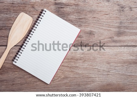 Close up cooking wooden spatula and lined paper on wooden table top view - stock photo