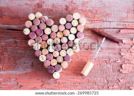 Close up Corks in Heart Shape and Wine Bottle Opener on Top of a Rustic Wooden Table for Love Concept. Captured in High Angle View. - stock photo