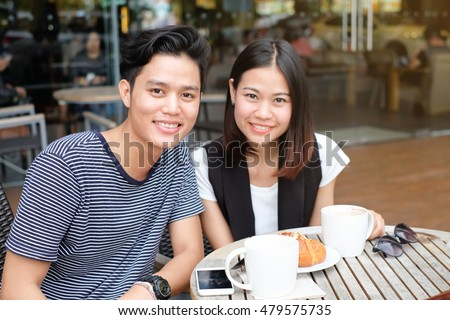 close up couple asian lovers smiling at outside restaurant.