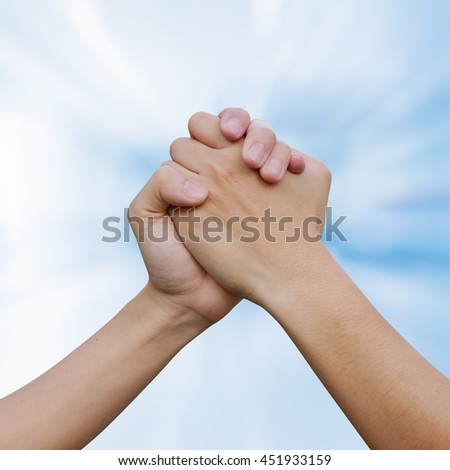 close up couple human handshake on blur blue teal color background:man hands shake for confident,success,victory,assurance concept:trust of humanity conceptual idea.action figure of powerful ideal - stock photo