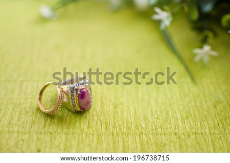 Close-Up Couple Wedding Ring On Green Carpet with Defocus Background, Selective Focus - stock photo