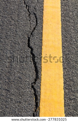 Close up cracked asphalt surface of the road with a yellow line Thailand. - stock photo
