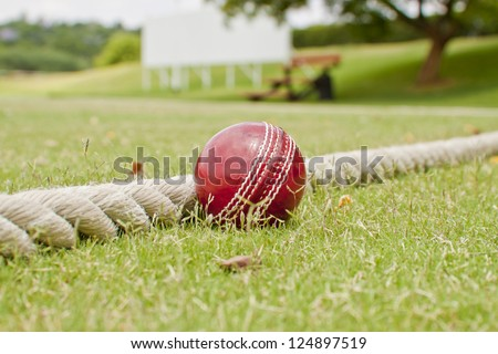 Close up Cricket ball on field touching boundary rope four runs with copy space - stock photo