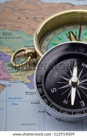Close-up cropped image of a compass over the world map - stock photo