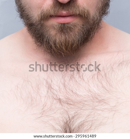 Close-up cropped image of man's face and chest isolated on grey. Srius man posing with his naked body.