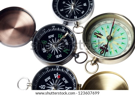 Close-up cropped shot of three different type of compass on white surface. - stock photo