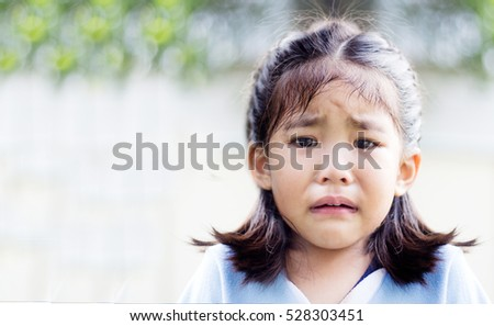 close up crying asian girl in park