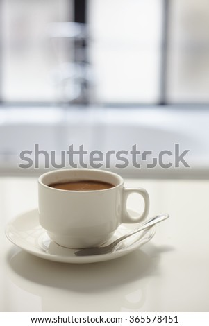 Close up cup of coffee in bathroom with bath in fuzzy background