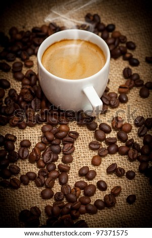 Close-up cup of hot coffee and coffee beans - stock photo