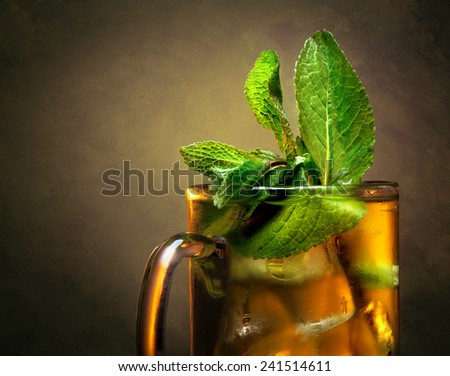 Close-up cup of tea with mint and ice on toned brown background - stock photo