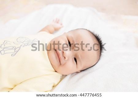 Close-up Cute Asian male baby lying on a towel is crying.  Blurred background.