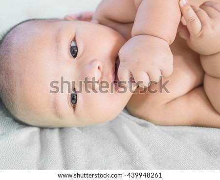Close-up Cute Asian male baby with a towel. 3 months baby boy lying on a towel. Healthy baby boy. Blurred background.