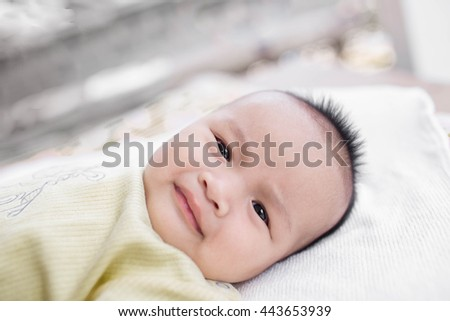 Close-up Cute Asian male baby with a towel on a Blurred background and bokeh. 3 months baby boy lying on a towel. Healthy baby boy.