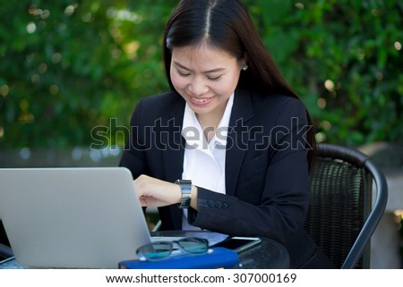 close up cute business woman looking on her watch , checking time for appointment at outside office : working woman love and happy to working, business woman concept,happy working concept. - stock photo