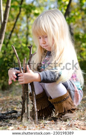 Close up Cute Little Blond Girl Playing with Dry Sticks on the Ground at the Forest. Captured During Autumn Season. - stock photo