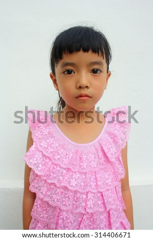 Close up cute little girl with Thai traditional dress staring blankly, selective focus - stock photo