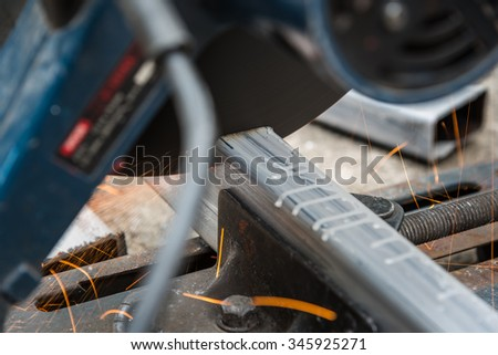 close up cutting a square metal and steel with compound mitre saw with circular blade