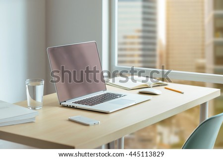Close up desktop businessman, Wooden desk with modern laptop, glass of water, modern cell phone, notebook. Desktop with a view of downtown, Sunrise, Shallow DOF. - stock photo