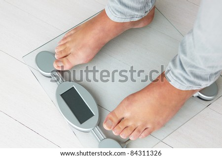 Close up detail girl weighing herself - stock photo