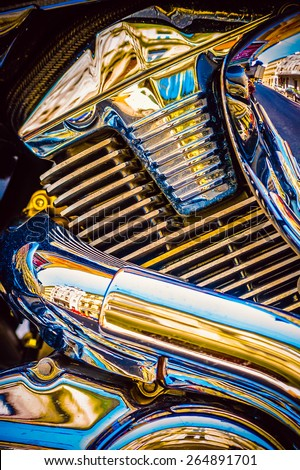 Close up detail image of shiny colorful chrome metal engine block of chopper motorcycle on the street - stock photo