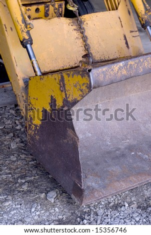 Close up detail of a bulldozer resting on gravel. - stock photo
