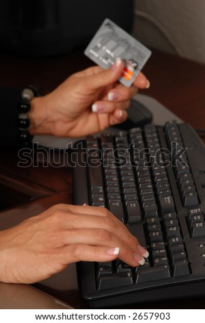 Close up detail of a business womans hands holding a credit card and making a purchase on line focal point on right hand with card OTF in the background