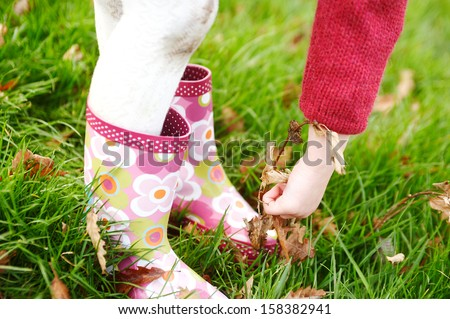 Close up detail of a little girl legs wearing dirty leotards and wellington boots, bending over and picking dry leaves from the green grass ground with her hand in a park, outdoors. - stock photo