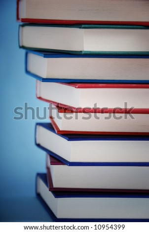 close up detail of a pile of books with blue background