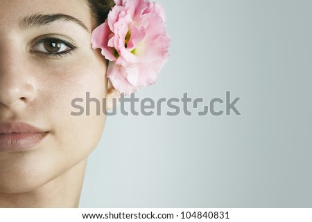 Close up detail of a young woman's half face wearing a tropical pink rose in her hair, on a plain background. - stock photo