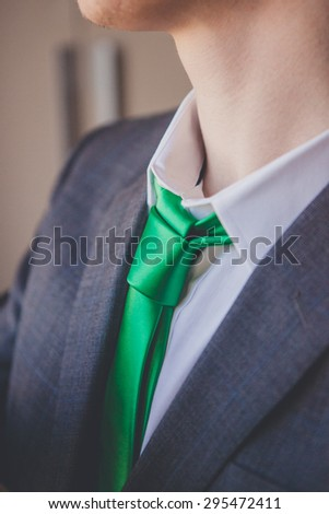 close up detail of an elegant groom's suit and green tie - stock photo