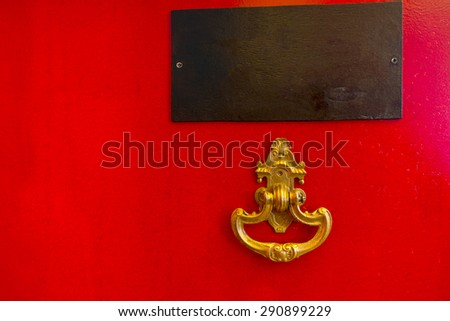 Close Up Detail of Bright Red Door with Golden Ornate Knocker and Blank Name Plate - stock photo