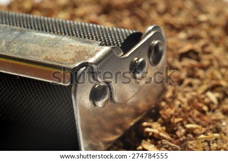 Close-up detail of cigarette maker machine on tobacco - stock photo