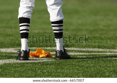 Close up detail of football referee's legs after a yellow penalty flag has been thrown.
