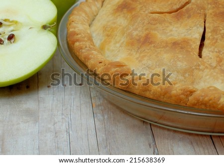 close up detail of freshly baked apple pie with a slice of a fresh green, Granny Smith apple beside it on a rustic table top.  The crust is golden brown and the pie is in a clear glass pie pan. - stock photo