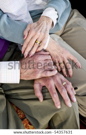 Close-up detail of hands of senior couple touching and resting on knees - stock photo