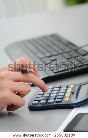 close up detail of hands typing on calculator with a desktop computer keyboard - stock photo