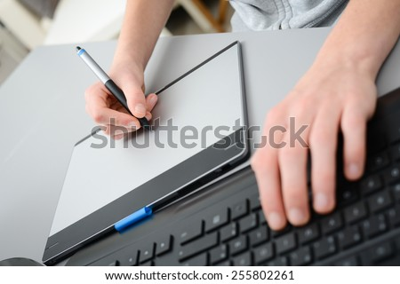 close up detail of hands working with graphic tablet and a desktop keyboard
