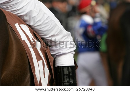Close-Up Detail of Jockey on Thoroughbred in Walking Ring of Race Track - stock photo