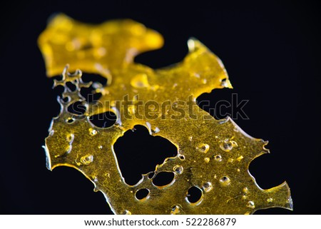 Close up detail of marijuana oil concentrate aka shatter isolated on black background