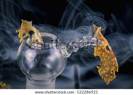 Close up detail of marijuana oil concentrate aka shatter isolated on black background with glass rig and smoke