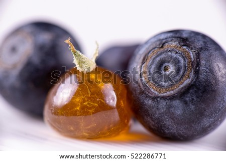 Close up detail of marijuana oil concentrate aka shatter on a plate with with blueberries
