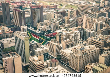 Close up detail of skyscrapers the business district of Johannesburg - Aerial view of modern buildings of the skyline in South Africa biggest city with southafrican flag painted on structure walls - stock photo