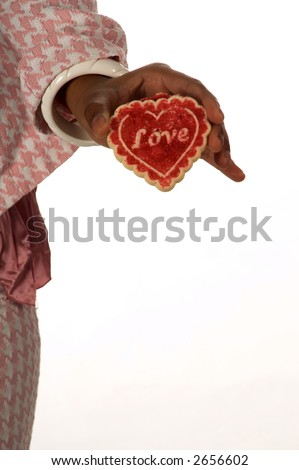Close up detail of the hand of a pretty young African American girl in a Herringbone suit holding a heart shaped cookie that says Love