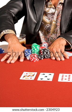 Close up detail of the hands of a male Texas Hold um poker player going all in on a red felt table