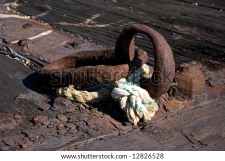close up detail of worn iron rings and rope on old dock
