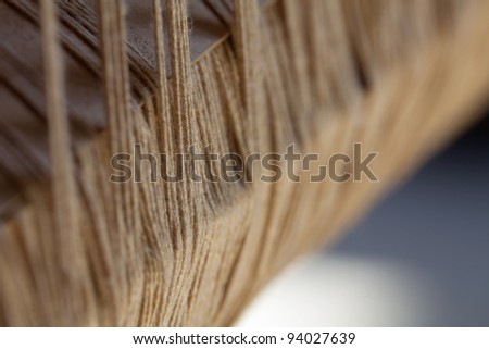 Close-up detail on the old loom - large fluffy yarn photographed from the side with a shallow depth of field - stock photo