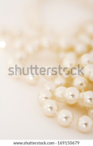 Close up detail still life view of an exclusive and luxurious natural pearl necklace on a white background. A string of quality pearls shining, interior. - stock photo
