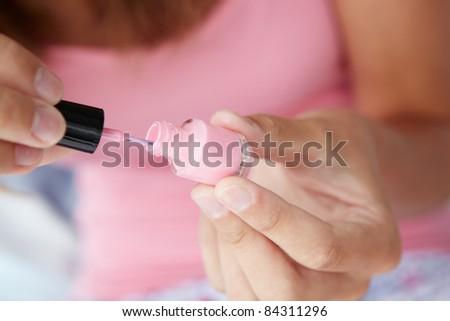 Close up detail teenage girl painting nails - stock photo