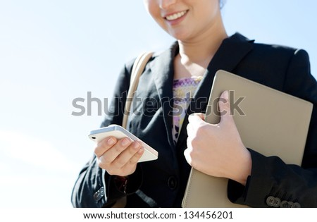 "Close up detail view of a businesswoman hand holding and using a digital ""smart phone"" while standing against a sunny blue sky. - stock photo"